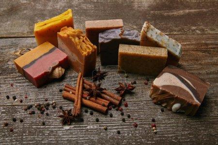 Photo pour Gros plan de morceaux de savon faits à la main avec des épices sur une table en bois rustique - image libre de droit