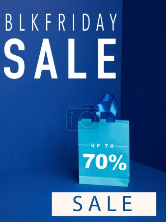 close up view of paper shopping bag on blue with blkfriday and 70 percents sale