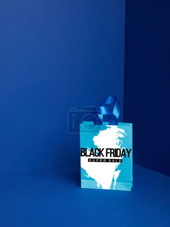 close up view of paper shopping bag on blue backdrop with black friday super sale