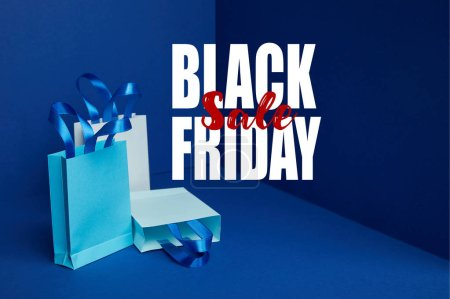 paper shopping bags arranged on blue with black friday sale