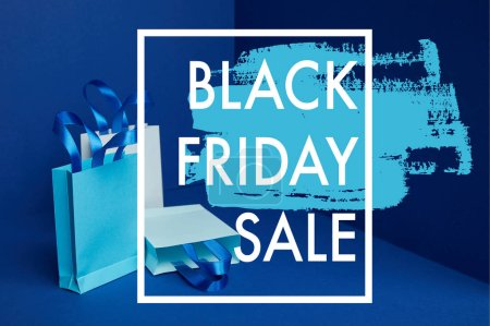 close up view of paper shopping bags arranged on blue backdrop with black friday sale