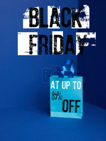 close up view of paper shopping bag on blue with black friday and 85 percents off discount