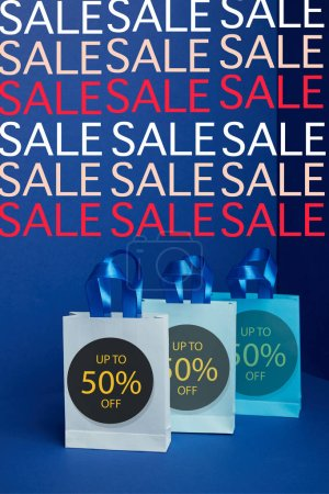close up view of paper shopping bags arranged on blue backdrop sale signs and 50 percents discount