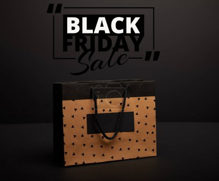 close up view of paper shopping bag on black with black friday sale