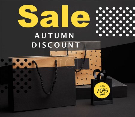 Photo for Close up view of shopping bags arranged on black background with autumn sale discount with 70 percents - Royalty Free Image