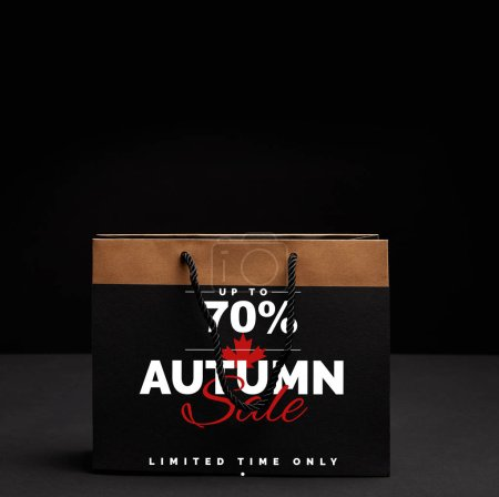 paper shopping bag on black backdrop with autumn sale and 70 percents discount