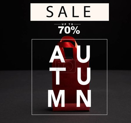 close up view of red paper shopping bag on black backdrop with autumn sale, 70 percents discount