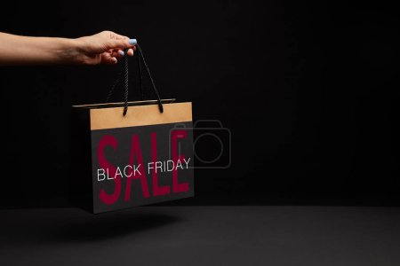 partial view of woman holding black shopping bag with black friday sale