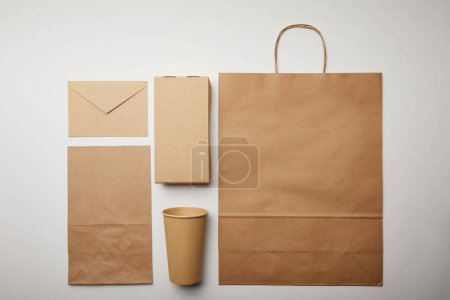 flay lay with envelope, paper cup, food delivery paper bag on white surface, minimalistic concept