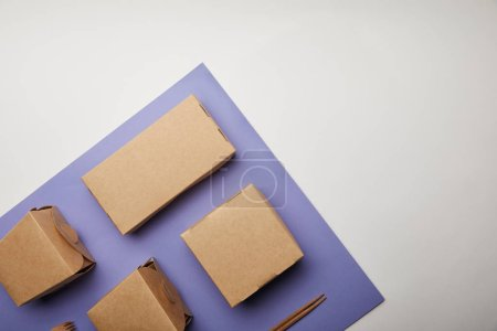 Photo for Elevated view of noodle boxes, chopsticks and food boxes on purple surface - Royalty Free Image