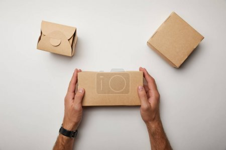 partial view of man sitting at table with cardboard food boxes