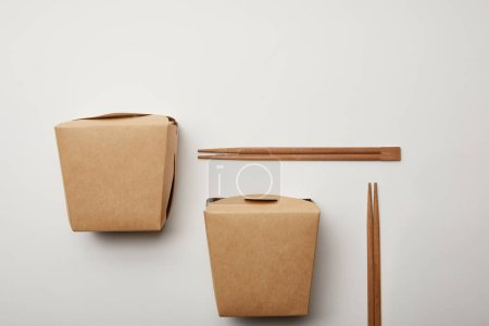 Photo for Flat lay with arranged wok boxes and chopsticks on white surface, minimalistic concept - Royalty Free Image