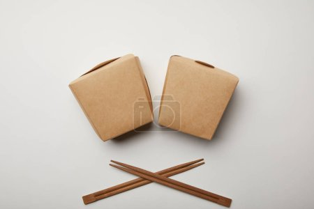 top view of arranged wok boxes and chopsticks on white surface, minimalistic concept