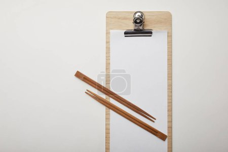 top view of blank menu and chopsticks on white surface, minimalistic concept