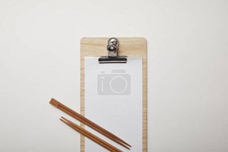 flat lay with blank menu and chopsticks on white surface, minimalistic concept