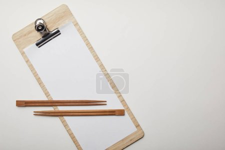 elevated view of blank menu and chopsticks on white surface, minimalistic concept