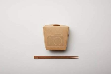 elevated view of arranged chopsticks and noodle box on white surface, minimalistic concept