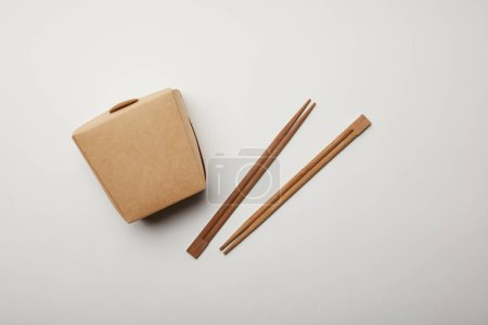 top view of arranged chopsticks and noodle box on white surface, minimalistic concept