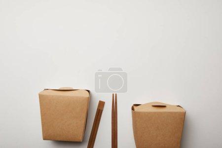 Photo pour Vue de dessus des baguettes disposées et des boîtes à nouilles sur surface blanche, concept minimaliste - image libre de droit