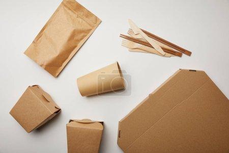 Photo pour Relief plat du couteaux jetables avec fourches, boîtes en papier café tasse et de la nourriture sur la surface blanche - image libre de droit