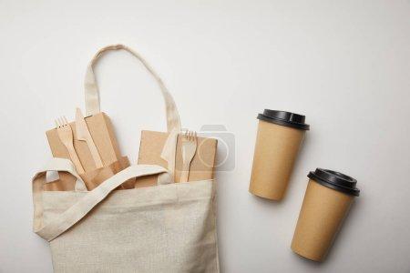 Foto de Vista elevada de bolsa de algodón con cajas de comida y dos tazas de café desechables sobre superficie blanca - Imagen libre de derechos