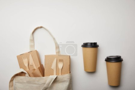 view from above of cotton bag with food boxes and two disposable coffee cups on white surface