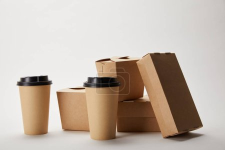 disposable coffee cups and cardboard food boxes on white