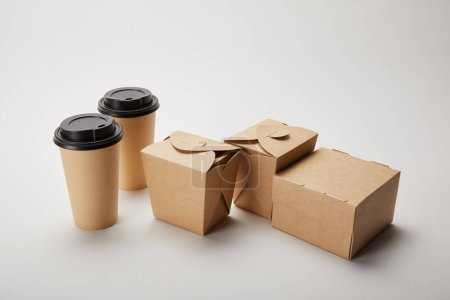 close up view of paper coffee cups and cardboard food boxes on white