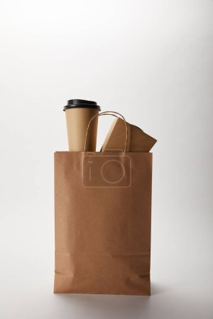 close up view of food delivery paper bag with disposable coffee cup and wok box on white