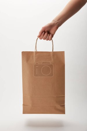 cropped image of woman holding paper bag with food delivery on white