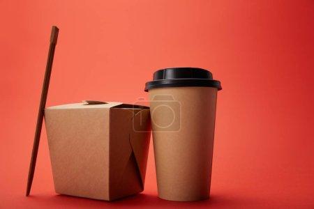 Photo pour Vue rapprochée de la boîte à nouilles, tasse de café en papier avec baguettes sur rouge, concept minimaliste - image libre de droit