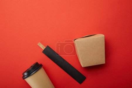 top view of noodle box, paper cup of coffee with chopsticks on red, minimalistic concept