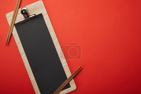 view from above of blank black menu and chopsticks on red surface, minimalistic concept
