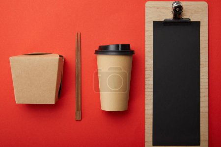 top view of arranged disposable coffee cup, chopsticks, wok box and blank menu on red surface