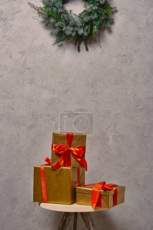golden Christmas gift boxes on chair under fir wreath in room