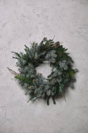 fir wreath for Christmas decoration hanging on grey wall in room