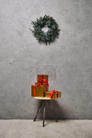 golden Christmas gift boxes with red ribbons on chair under fir wreath in room