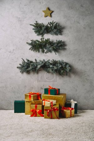 Photo pour Sapin de Noël fait main accroché sur un mur gris, coffrets-cadeaux sur tapis de chambre - image libre de droit