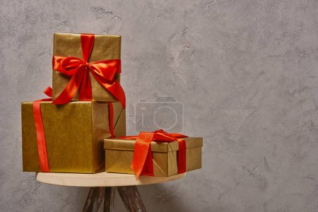 golden Christmas gift boxes on chair near grey wall in room