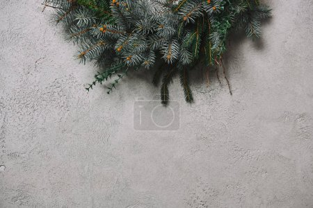 Foto de Imagen recortada de corona de abeto para la decoración de Navidad colgado en una pared gris en sala - Imagen libre de derechos