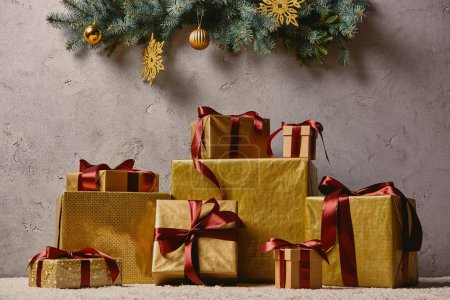 pile of golden Christmas gift boxes on carpet in room under christmas tree