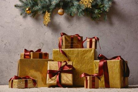 Photo pour Pile de boîtes cadeaux de Noël doré sur le tapis dans la chambre sous l'arbre de Noël - image libre de droit