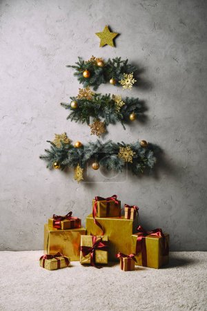 handmade Christmas tree and star hanging on grey wall, gift boxes on floor in room