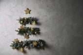 handmade Christmas tree hanging on grey wall in room