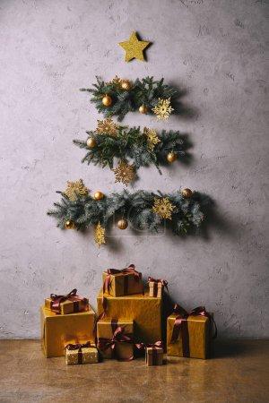 Photo pour Arbre de Noël à la main fait de brindilles accroché sur un mur gris, coffrets d'étage dans la chambre - image libre de droit