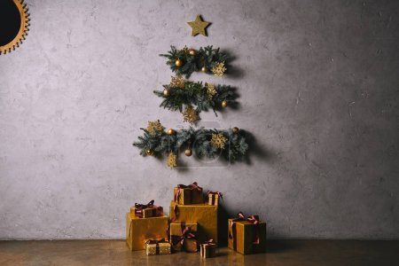 Photo for Handmade Christmas tree hanging on grey wall, gift boxes on floor in room - Royalty Free Image