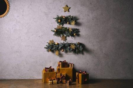 Photo pour Sapin de Noël fait main accroché sur un mur gris, coffrets d'étage dans la chambre - image libre de droit