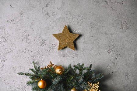 Foto de Estrella de Navidad oro colgar en la pared gris sobre el árbol de Navidad en la sala de - Imagen libre de derechos
