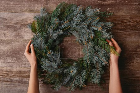 cropped image of woman holding christmas fir wreath at wooden table