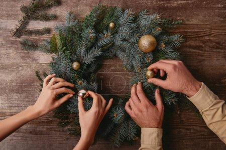 Photo pour Cropped image du couple décoration guirlande de sapin de Noël ensemble - image libre de droit